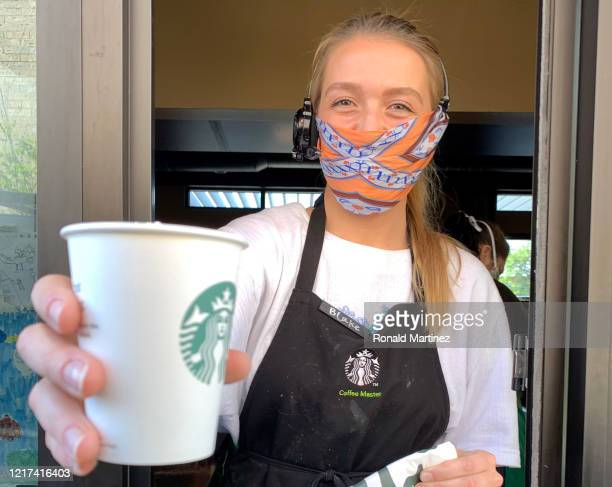 Starbucks employee wears a facial covering while working the drive-thru during the coronavirus pandemic on April 07, 2020 in Dallas, Texas. Starbucks...