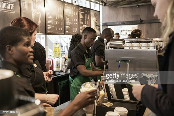 Starbucks employees serve customers during the official opening of South Africa's first Starbucks store also the US coffeehouse chain's first store...
