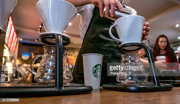 Starbucks staff make coffee behind counter Starbucks already has nearly 2000 stores in mainland China and plans to have 3400 by 2019 laying the...