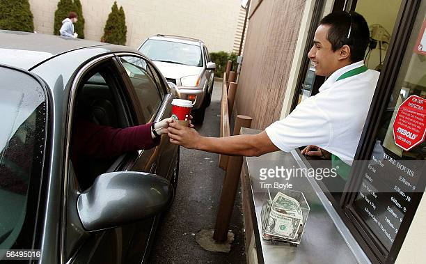 Starbucks worker Freddie Arteaga assists a customer with her drink order at a Starbucks drivethru December 28 2005 in Wheeling Illinois Starbucks...