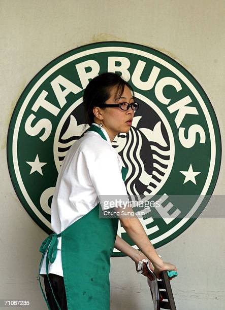 Starbucks worker walks past the company logo at a coffee store on May 31 2006 in Seoul South Korea The National Tax Service has launched its first...