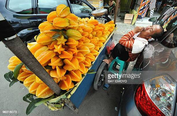 A starfruit vendor falls asleep while waiting for customers in Jakarta on January 31 2010 Indonesia�s economy has returned back on track following a...