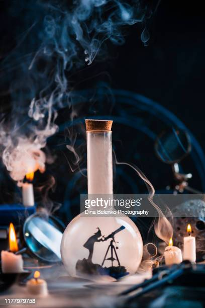 stargazer silhouette in a laboratory flash on a magical workplace with smoke, candles and meteor. astrology and astronomy concept with copy space - khabarovsk krai stock pictures, royalty-free photos & images