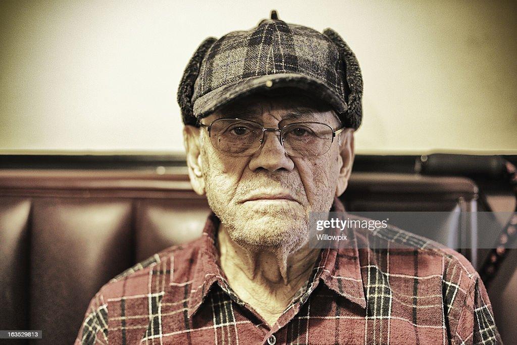 Staring Senior Man Wearing Plaid Hunter Cap : Stock Photo