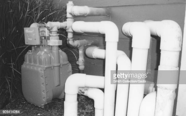 Starkly lit black and white image of a maze of natural gas pipes leading to a Pacific Gas and Electric smart gas meter part of a smart grid program...