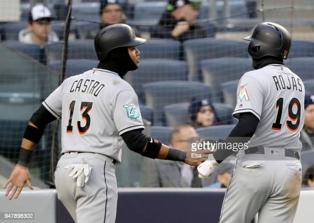 Starlin Castro and Miguel Rojas of the Miami Marlins celebrate after they both scored on a hit by teammate JT Realmuto in the first inning against...