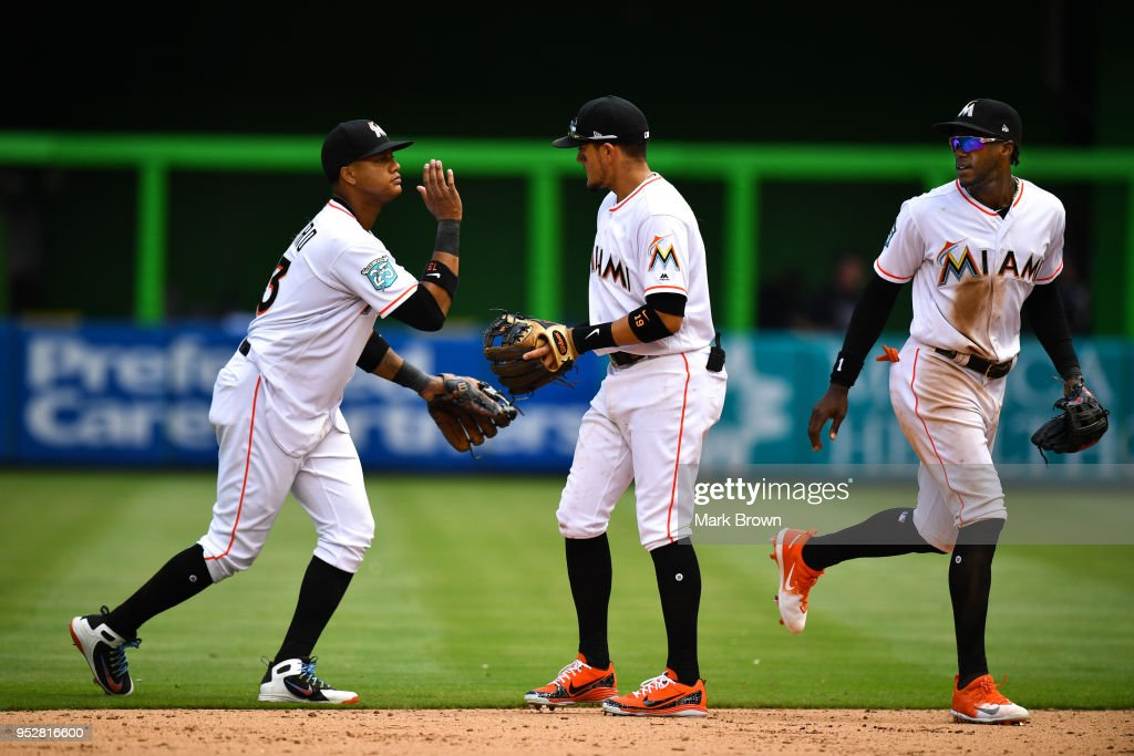 Starlin Castro #13, Miguel Rojas #19, and Cameron Maybin #1 of the Miami Marlins celebrate the win at the end of the game after beating the Colorado Rockies at Marlins Park on April 29, 2018 in Miami, Florida.