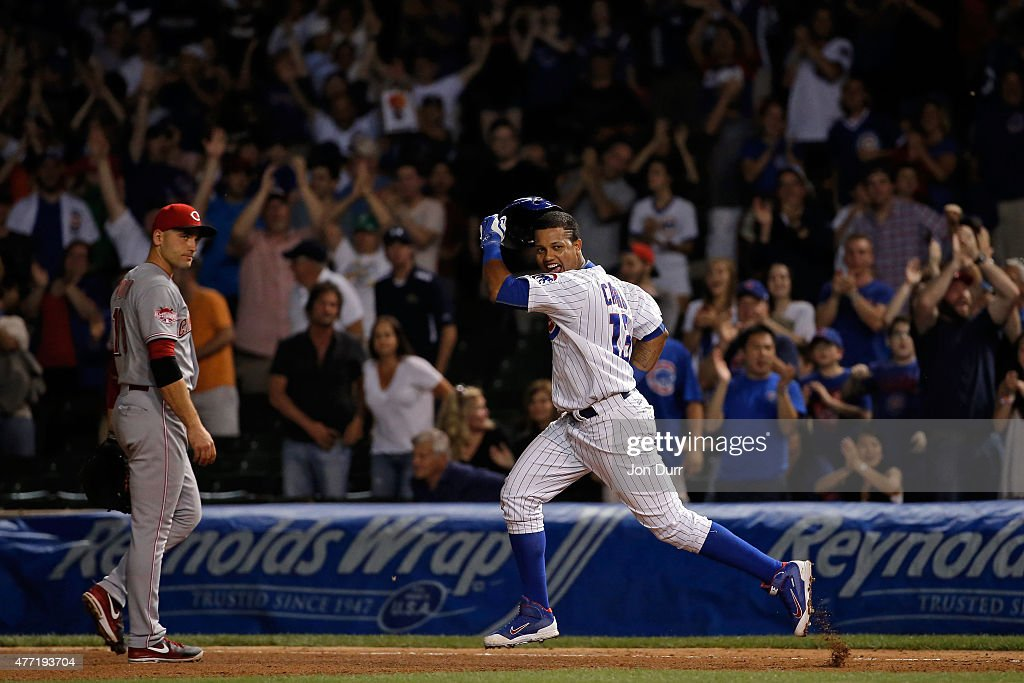 Starlin Castro #13 of the Chicago Cubs celebrates after hitting a walkoff one run RBI single against the Cincinnati Reds during the eleventh inning as Joey Votto #19 of the Cincinnati Reds looks on at Wrigley Field on June 14, 2015 in Chicago, Illinois. The Chicago Cubs won 2-1 in eleven innings.