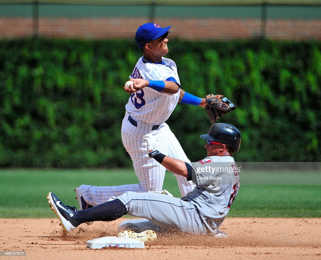 Starlin Castro #13 of the Chicago Cubs forces out Michael Brantley #23 of the Cleveland Indians during the seventh inning on August 24, 2015 at Wrigley Field in Chicago, Illinois.
