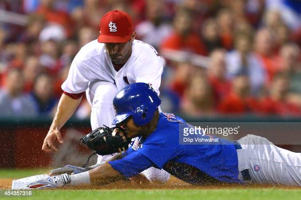 Starlin Castro of the Chicago Cubs is tagged out at third base by Matt Carpenter of the St Louis Cardinals while trying to run out a triple in the...