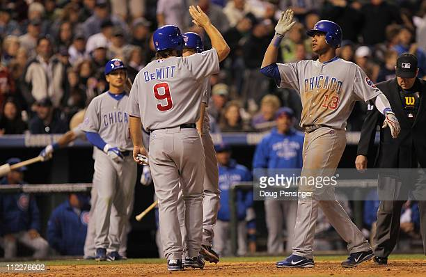 Starlin Castro of the Chicago Cubs is welcomed home after his three RBI homerun by Koyie Hill of the Cubs and Blake DeWitt of the Cubs whos scored on...