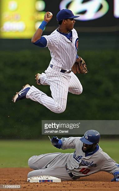 Starlin Castro of the Chicago Cubs leaps over Tony Gwynn of the Los Angeles Dodgers to try and turn a double play at Wrigley Field on May 6 2012 in...