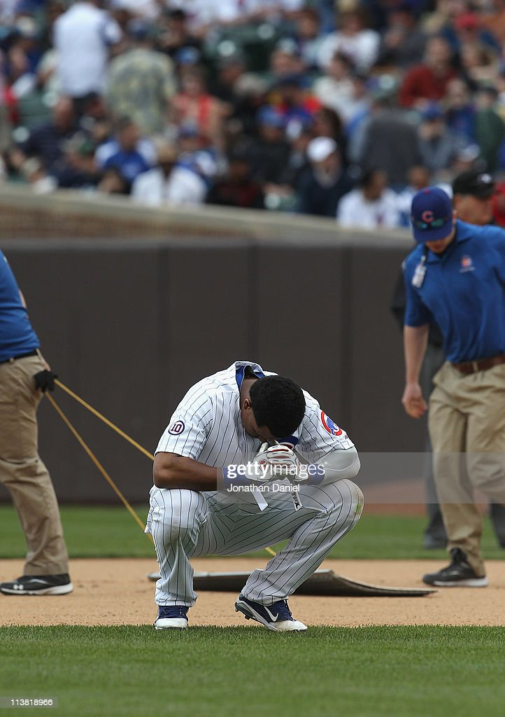 Starlin Castro #13 of the Chicago Cubs reacts after grounding out with the bases loaded to end the 6th inning against the Cincinnati Reds as members of the grounds crew drag in the infield dirt at Wrigley Field on May 6, 2011 in Chicago, Illinois. The Reds defeated the Cubs 5-4.