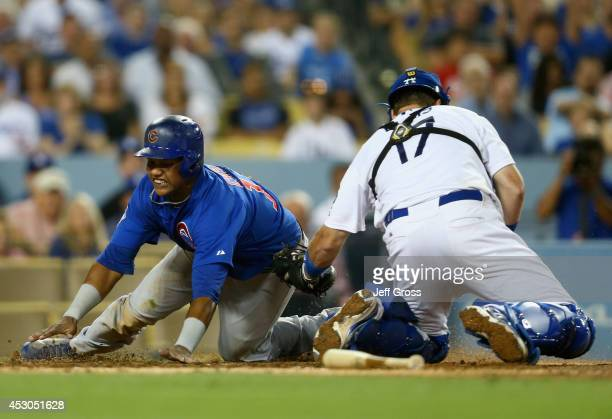 Starlin Castro of the Chicago Cubs slides safely past the tag of catcher AJ Ellis of the Los Angeles Dodgers and scores a run on a sacrifice fly in...