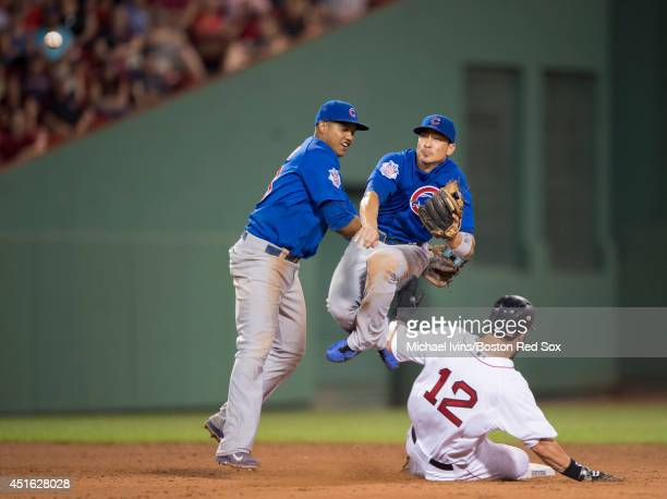 Starlin Castro of the Chicago Cubs tries to stay out of the way of Darwin Barney of the Chicago Cub as he attempts to complete a double play over...