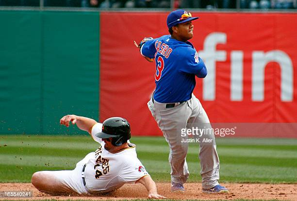 Starlin Castro of the Chicago Cubs turns a double play to end the game in front of Gaby Sanchez of the Pittsburgh Pirates during the game on April 4...