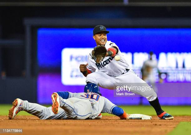 Starlin Castro of the Miami Marlins attempts to tag Michael Conforto of the New York Mets in the sixth inning against the during the game at Marlins...