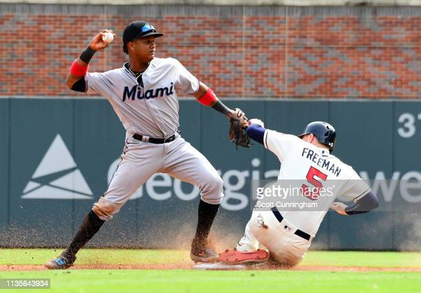 Starlin Castro of the Miami Marlins attempts to turn a ninth inning double play against Freddie Freeman of the Atlanta Braves at SunTrust Park on...