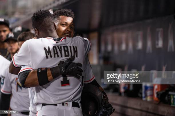 Starlin Castro of the Miami Marlins celebrates in the dugout with Cameron Maybin after hitting a home run during the game against the Milwaukee...