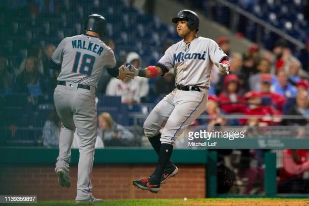 Starlin Castro of the Miami Marlins celebrates with Neil Walker after hitting a two run home run in the top of the tenth inning against the...
