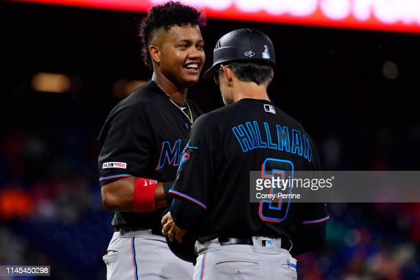Starlin Castro of the Miami Marlins smiles after hitting with first base coach Trey Hillman during the fourth inning at Citizens Bank Park on April...