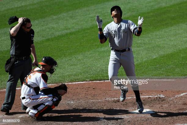Starlin Castro of the New York Yankees celebrates in front of catcher Caleb Joseph of the Baltimore Orioles and home plate umpire Sean Barber after...