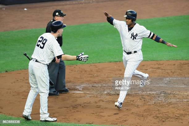 Starlin Castro of the New York Yankees celebrates with Todd Frazier after scoring on a Greg Bird single during the second inning against the Houston...