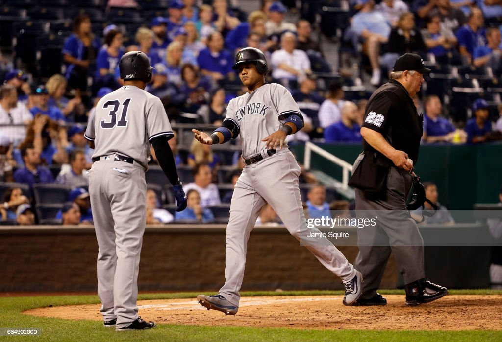 Starlin Castro #14 of the New York Yankees is congratulated by Aaron Hicks #31 after crossing home plate to score the Yankees only run and avoid a shutout during the 9th inning of the game against the Kansas City Royals at Kauffman Stadium on May 18, 2017 in Kansas City, Missouri.