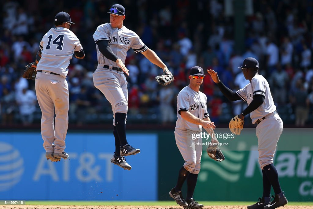 Starlin Castro #14 of the New York Yankees leaps with Aaron Judge #99 of the New York Yankees as they celebrate the win over the Texas Rangers at Globe Life Park in Arlington on September 9, 2017 in Arlington, Texas.
