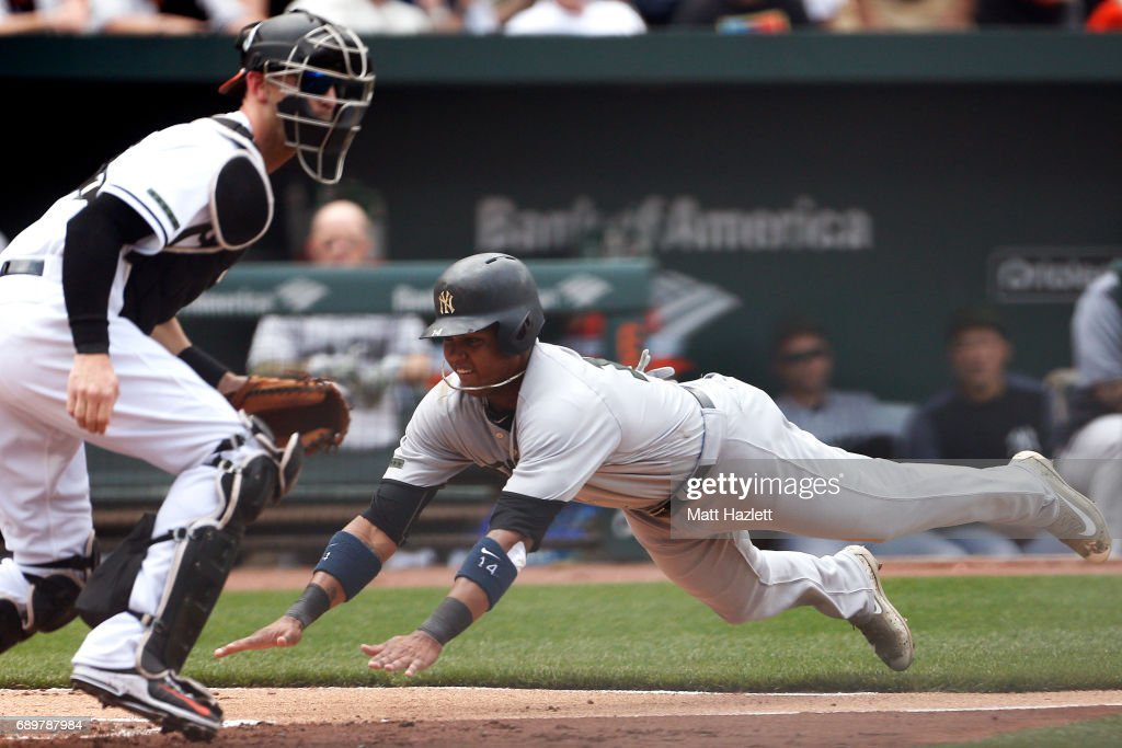 Starlin Castro #14 of the New York Yankees scores against Caleb Joseph #36 of the Baltimore Orioles off of a Aaron Hicks #31 of the New York Yankees (not pictured) sacrifice fly during the second inning at Oriole Park at Camden Yards on May 29, 2017 in Baltimore, Maryland. MLB players across the league are wearing special uniforms to commemorate Memorial Day.