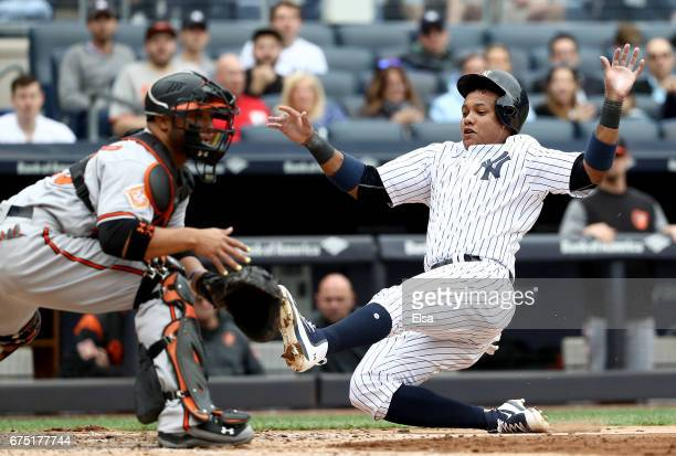 Starlin Castro of the New York Yankees slides hom safely as Welington Castillo of the Baltimore Orioles is unable to make the tag in the third inning...