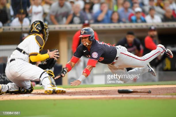 Starlin Castro of the Washington Nationals dives trying to score against Victor Caratini of the San Diego Padres in the second inning at Petco Park...