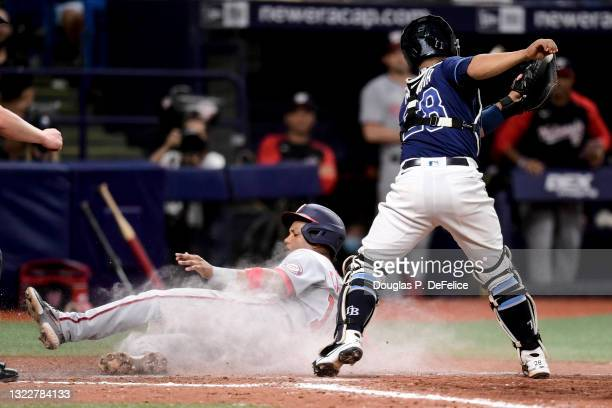 Starlin Castro of the Washington Nationals slides safely into home plate under the glove of Francisco Mejia of the Tampa Bay Rays on an sacrifice fly...