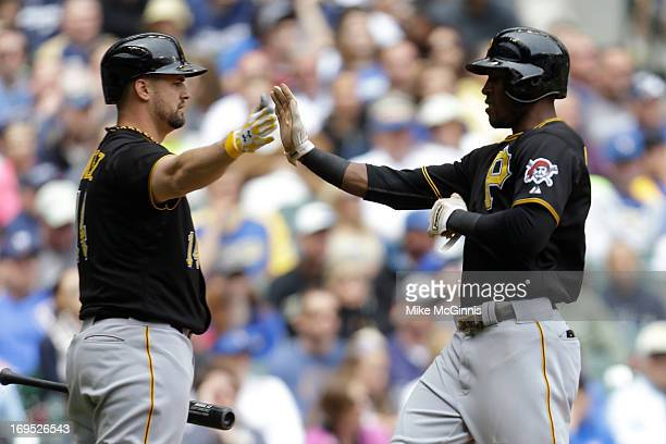 Starlin Marte of the Pittsburgh Pirates celebrates with Gaby Sanchez after reaching on a sacrifice fly hit by Garrett Jones in the top of the third...