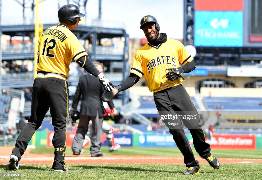 Starling Marte #6 celebrates with Corey Dickerson #12 of the Pittsburgh Pirates after scoring during the fifth inning against the Cincinnati Reds at PNC Park on April 8, 2018 in Pittsburgh, Pennsylvania.