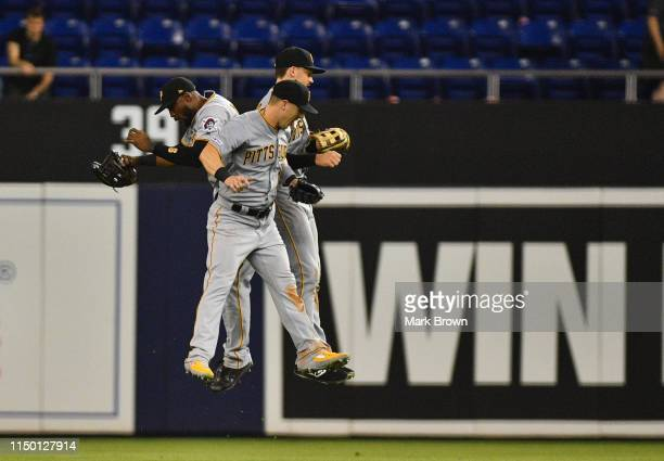 Starling Marte, Corey Dickerson, and Bryan Reynolds of the Pittsburgh Pirates celebrate the win against the Miami Marlins at Marlins Park on June 14,...
