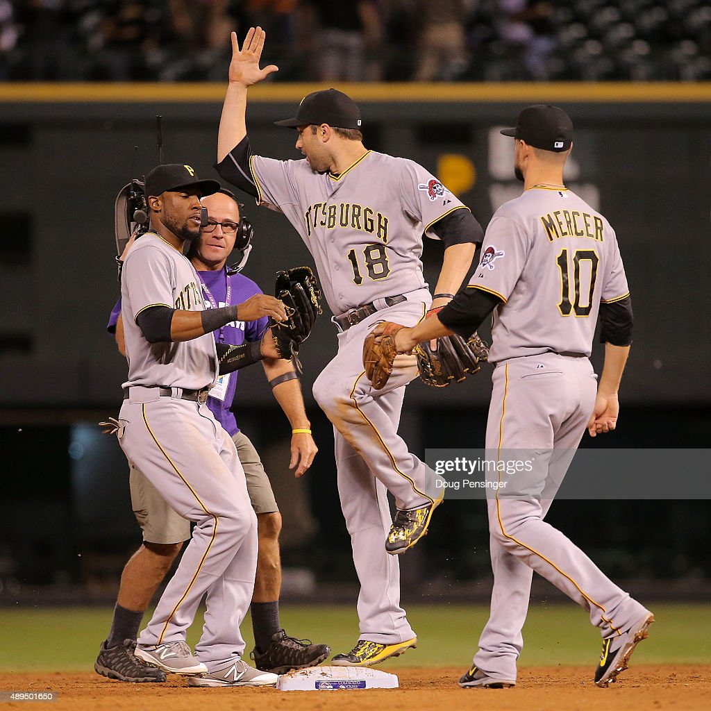 Starling Marte #6, Neil Walker #18 and Jordy Mercer #10 of the Pittsburgh Pirates celebrate their 9-3 victory over the Colorado Rockies at Coors Field on September 21, 2015 in Denver, Colorado.