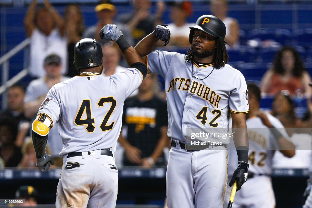Starling Marte #6 of the Pittsburgh Pirates celebrates with Josh Bell #55 after hitting a solo home run in the ninth inning against the Miami Marlins at Marlins Park on April 15, 2018 in Miami, Florida. All players are wearing #42 in honor of Jackie Robinson Day.