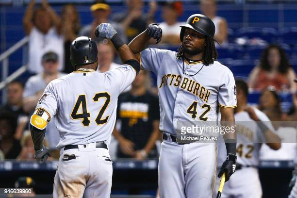 Starling Marte of the Pittsburgh Pirates celebrates with Josh Bell after hitting a solo home run in the ninth inning against the Miami Marlins at...