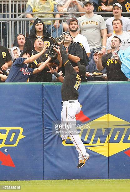 Starling Marte of the Pittsburgh Pirates comes up short on a home run by Brandon Moss 44 of the Cleveland Indians in the first inning during the...