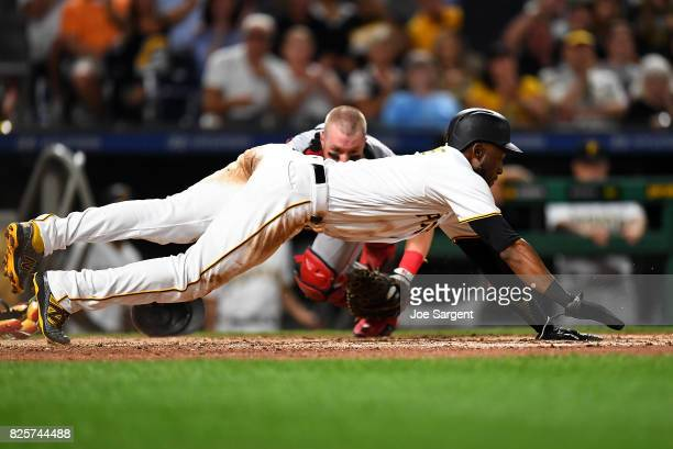 Starling Marte of the Pittsburgh Pirates dives back to home plate in front of Tucker Barnhart of the Cincinnati Reds during the sixth inning against...
