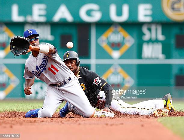 Starling Marte of the Pittsburgh Pirates safely steals second base in front of Jimmy Rollins of the Los Angles Dodgers in the first inning during the...