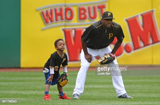 Starling Marte of the Pittsburgh Pirates shags fly balls in the outfield with his son Smerling Marte during batting practice before the game against...