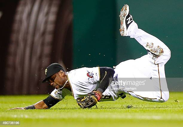 Starling Marte of the Pittsburgh Pirates slides but fails to come up with a catch in left field in the 8th inning against the St Louis Cardinals...
