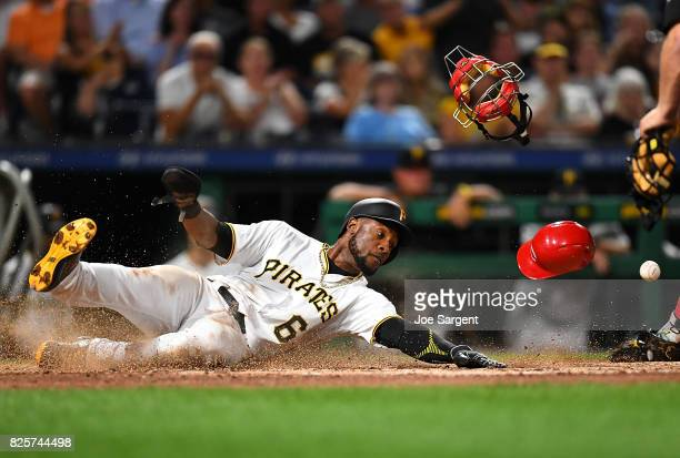 Starling Marte of the Pittsburgh Pirates slides into home plate during the sixth inning against the Cincinnati Reds at PNC Park on August 2 2017 in...