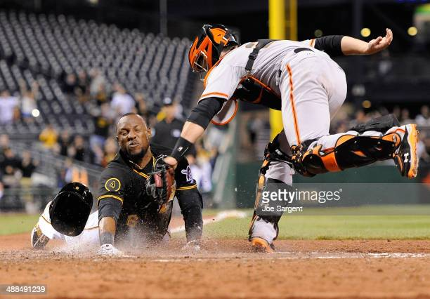 Starling Marte of the Pittsburgh Pirates slides safely into home plate to score the game winning run in front of Buster Posey during the ninth inning...