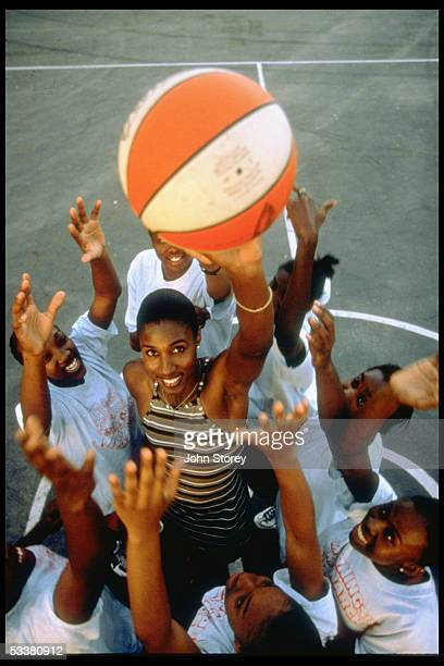 Star/model Lisa Leslie shooting hoops with young girls.