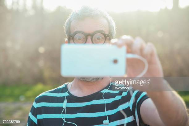 Starring man taking picture of viewer with smartphone