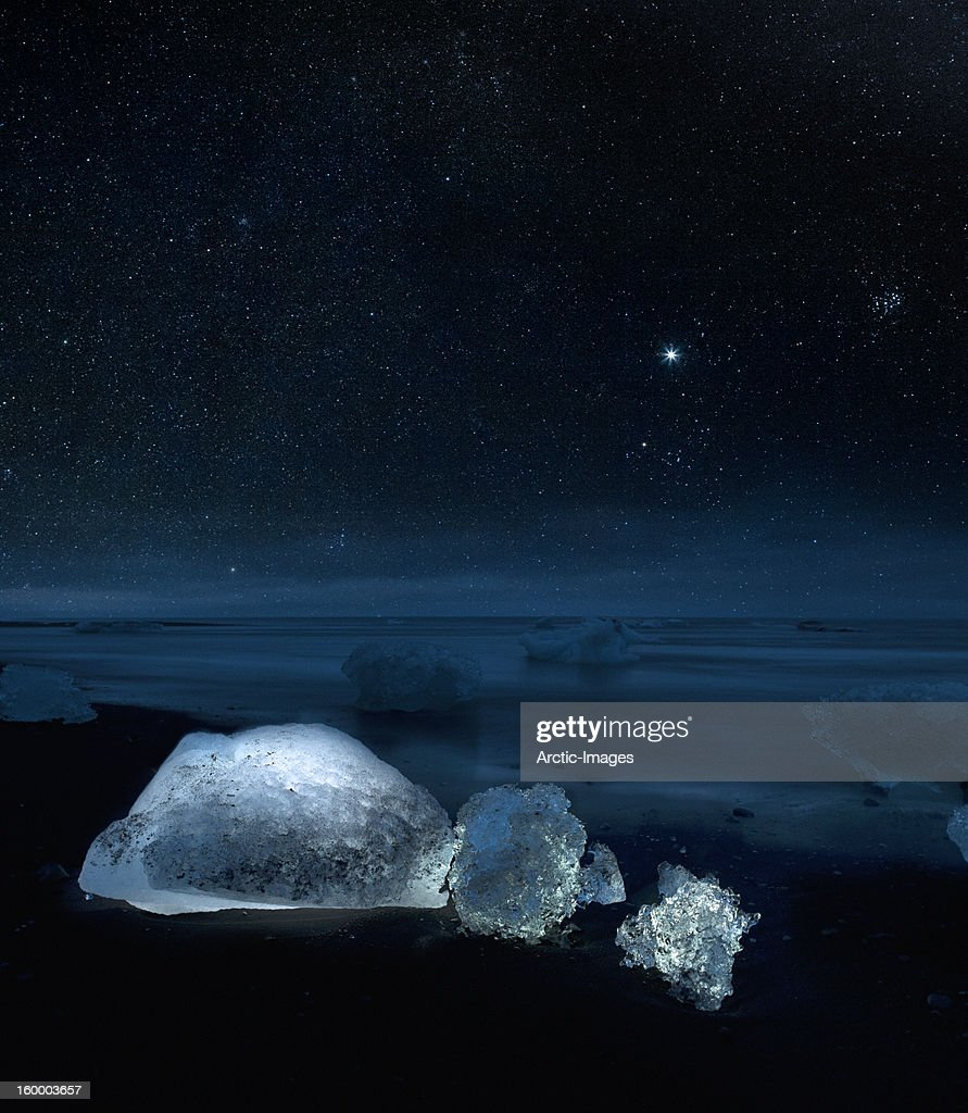 Starry night over ice on black sand beach : Foto de stock