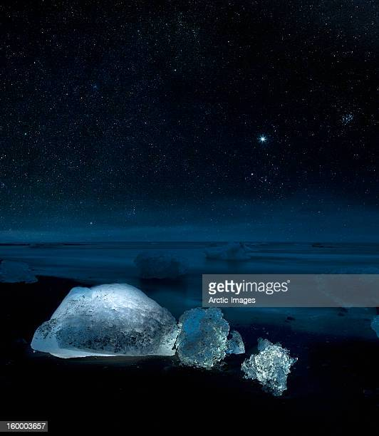 Starry night over ice on black sand beach